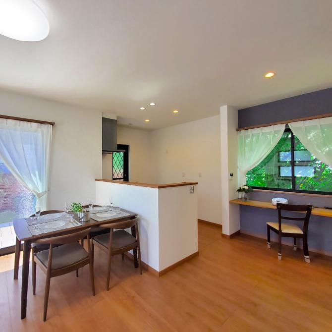緑が映える素敵な窓辺のカウンターがある 開放感あふれる吹き抜けリビングの家